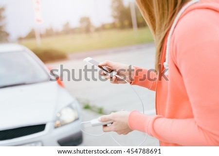 Woman playing mobile games on smartphone in the street