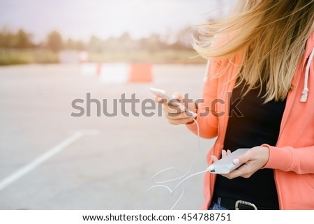 Woman playing mobile games on smartphone on the street