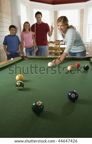 Woman playing pool with family in background. Vertically framed shot. - stock photo
