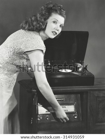 Woman playing record album on phonograph
