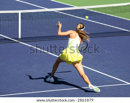 Woman playing tennis at the professional tournament - stock photo