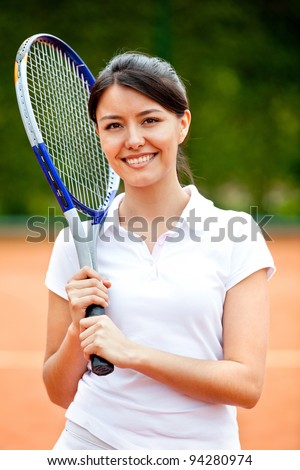 Woman playing tennis holding a racket and smiling - stock photo