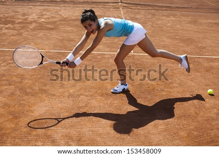 Woman playing tennis in summer - stock photo