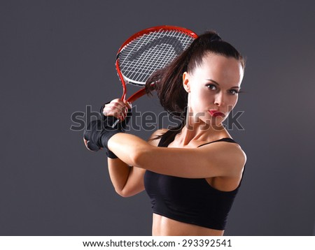 Woman playing tennis on gray background .