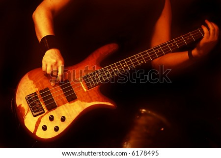 woman playing the guitar in a band isolated on black background - stock photo