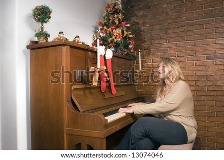 Woman playing the piano at Christmas time. Horizontally framed shot. - stock photo