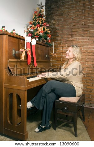 Woman playing the piano at Christmas time. Vertically framed shot. - stock photo