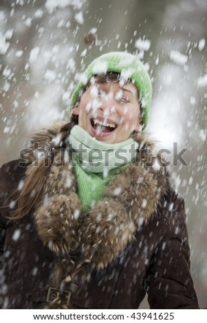woman playing with falling snow in the winter forest