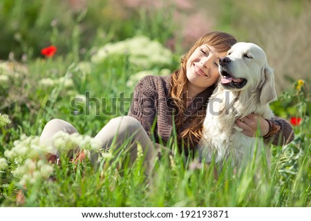 Woman playing with her dog outdoors - stock photo