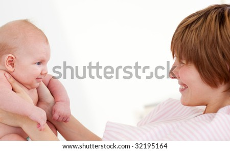 Woman playing with her newborn baby in hospital - stock photo