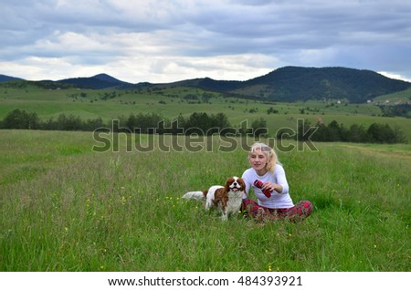 Woman playing with her pet dog (Cavalier King Charles Spaniel) on a meadow with hills and cloudy sky in background