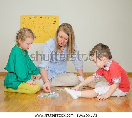 Woman plays with children at home. - stock photo