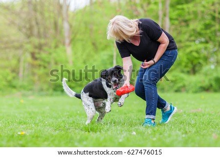 woman plays with her mixed breed dog outdoors