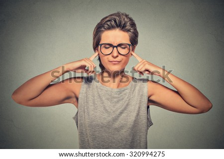 Woman plugging ears with fingers doesn't want to listen eyes closed ignoring stressful unpleasant situation conflict
