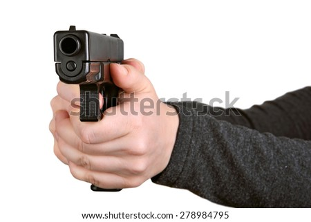 Woman pointing a gun at the camera on a white background. Focus on the front of the gun.