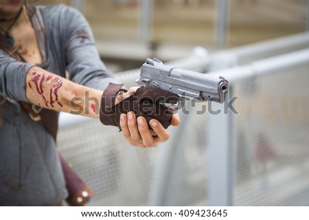 Woman pointing a 9mm pistol - stock photo