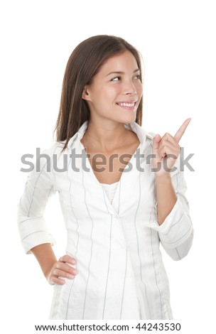 Woman pointing and looking to the side. Casual young businesswoman in white shirt and smiling at copy space. Beautiful young mixed race chinese / caucasian isolated on seamless white background. - stock photo
