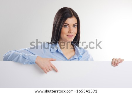 Woman pointing at a blank board - stock photo