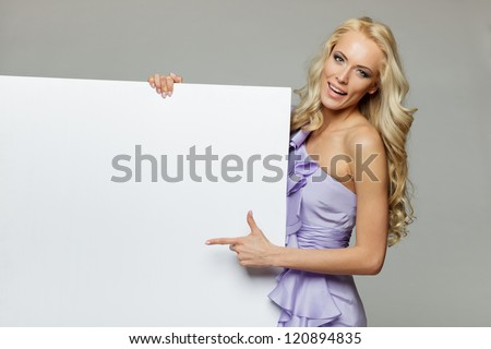 Woman pointing at a blank board over gray background - stock photo
