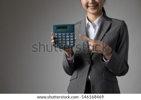 Woman pointing at a calculator, computer, guide