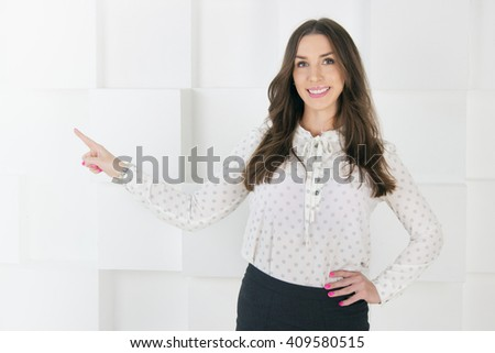 Woman pointing at copy space and looking at camera. Smiling casual young businesswoman in white shirt and dark skirt on abstract background. - stock photo
