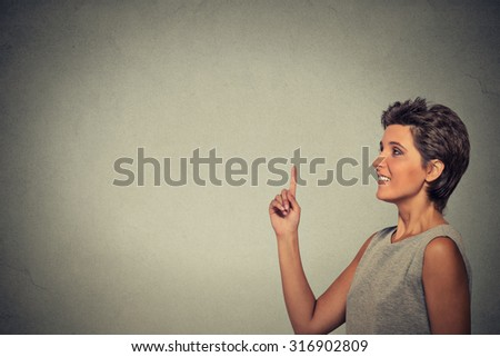 woman pointing at copyspace isolated on gray wall background - stock photo