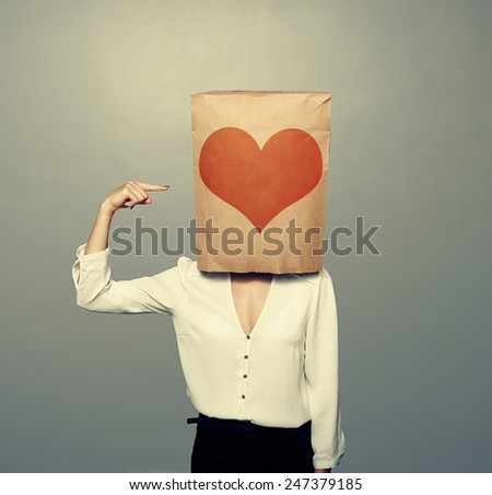 woman pointing at heart on paper bag over dark background - stock photo