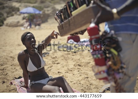 Woman pointing at imitation products at the beach - stock photo