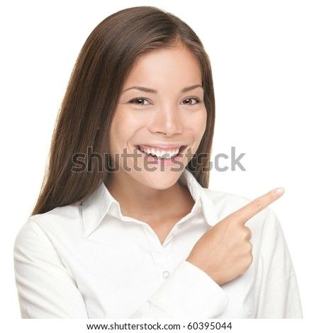 Woman pointing. Closeup portrait of young smiling woman pointing at copy space. Isolated on white background. Asian / Caucasian female model. - stock photo
