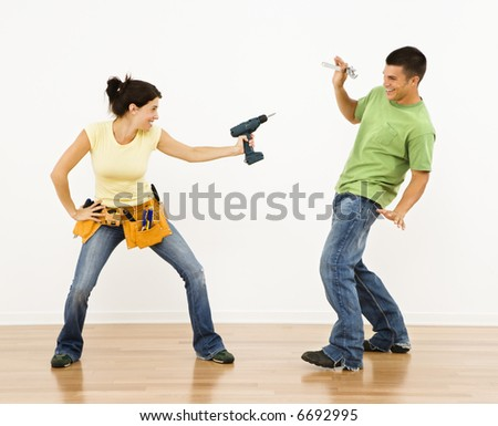 Woman pointing drill playfully at man smiling and laughing in home.