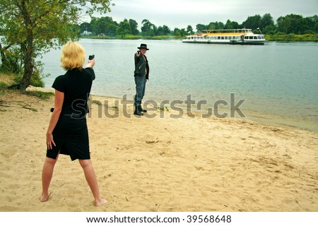 woman pointing gun at man wearing cowboy hat, river and ship in background - stock photo