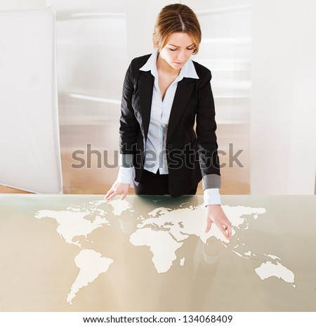 Woman Pointing On Transparent Screen Showing World Map - stock photo