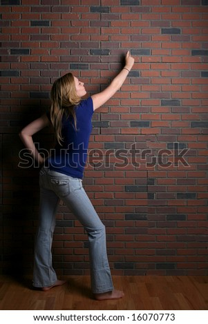 woman pointing to copy space on brick wall - stock photo