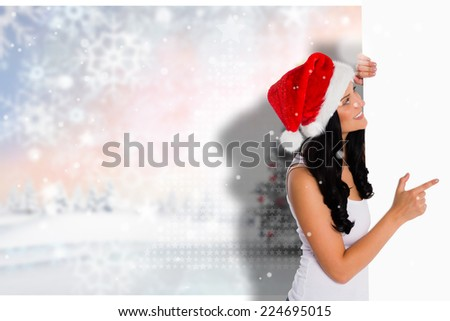 Woman pointing to large sign against blurry christmas scene - stock photo