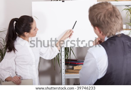 woman pointing with a pen on white billboard in office - stock photo