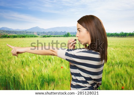 Woman pointing with her finger and using a whistle. Over meadow background - stock photo