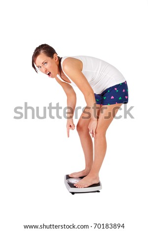 Woman points angry at her scale - stock photo