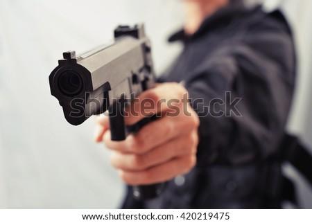 woman police hand hold gun - stock photo