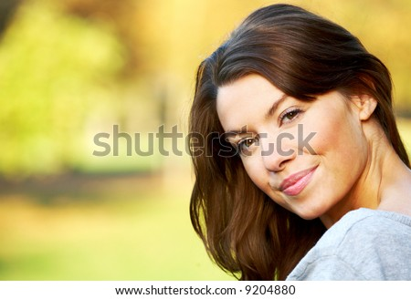 woman portirat smiling outdoors on a sunny day - stock photo