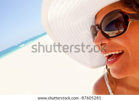 Woman portrait at the beach looking very happy - stock photo