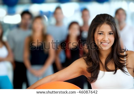 Woman portrait at the gym with a pilates ball in front of a group - stock photo