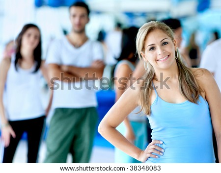 Woman portrait at the gym with people behind her - stock photo