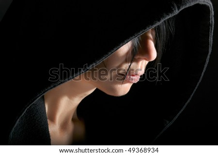 Woman portrait in low key with contour from hood - stock photo