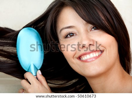 Woman portrait in the bathroom brushing her hair