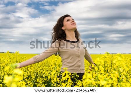 woman portrait in yellow flower field - stock photo