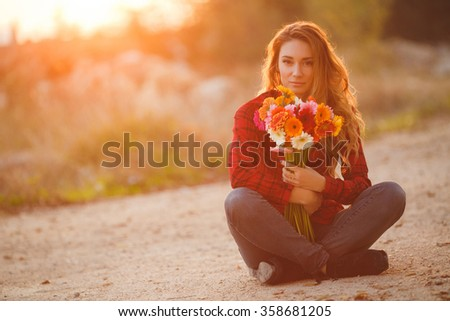 woman portrait outdoor in sunset light. woman with flower bouquet. Portrait of the beautiful girl close-up, the wind fluttering hair. - stock photo