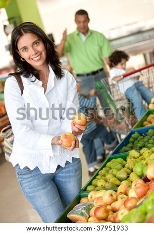 Woman portrait shopping at the supermarket and smiling - stock photo