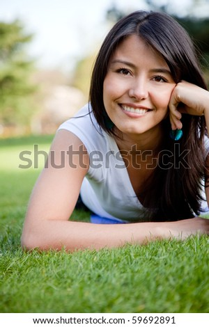 Woman portrait smiling lying on grass - outdoors - stock photo