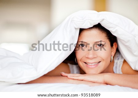 Woman portrait under the sheets looking happy - stock photo