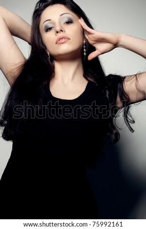 woman portrait wearing black dress with shadow on background